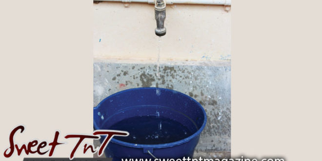 Dripping pipe filling blue bucket during Dry Season, drought, lack of water, water conservation, shortage in Sweet T&T, Sweet TnT Magazine, Trinidad and Tobago, Trini, vacation, travel