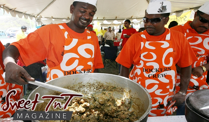 Chefs of Dockers crew cooking curried duck in big pot at cook-out wearing orange t shirts and aprons with white hats with ducks in Sweet T&T, Sweet TnT Magazine, Trinidad and Tobago, Trini, vacation, travel Recipes