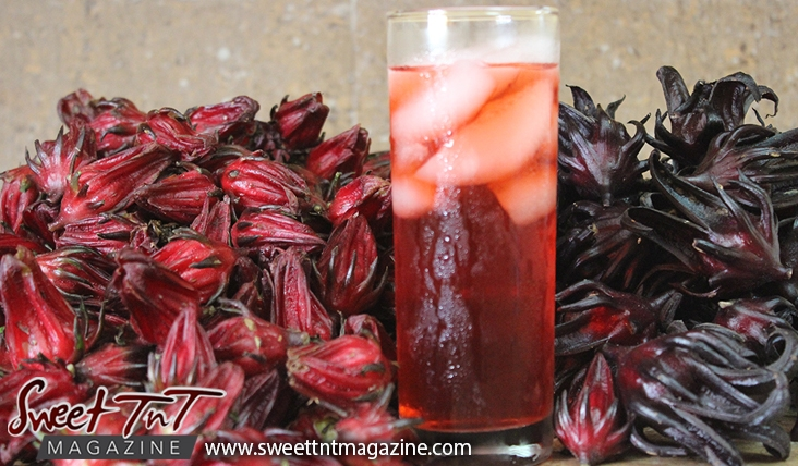 Sorrel or roselle drink or juice in glass with ice with red fruit for Christmas season or health benefits for cholesterol, blood pressure, bladder infections, constipation, maylase, use recipe for good taste and health benefits in in Sweet T&T, Sweet TnT, Trinidad and Tobago, Trini, vacation, travel